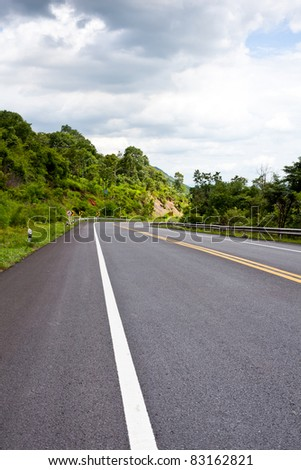 Asphalt road along with tropical forest zigzag ahead.