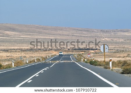 Asphalt road among the desert and hills.
