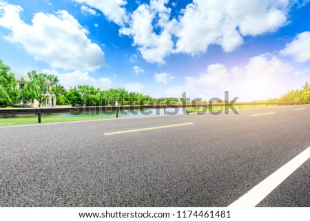Asphalt road and apartment buildings with woods in the city suburbs #1174461481