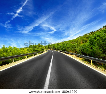 Asphalt road and blue sky with clouds
