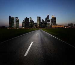 Asphalt road and city with illuminated buildings on the horizon
