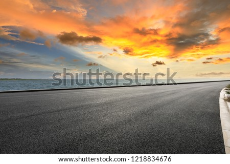 Asphalt road and dramatic sky with coastline at sunset #1218834676