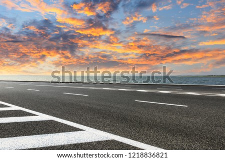 Asphalt road and dramatic sky with coastline at sunset #1218836821