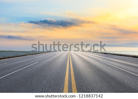 Asphalt road and dramatic sky with coastline at sunset #1218837142