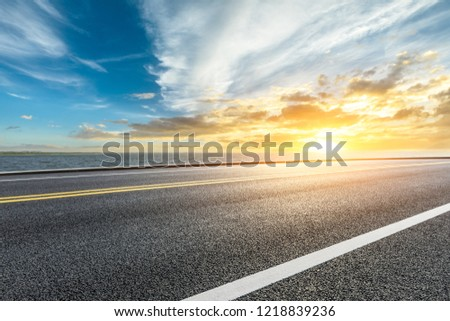 Asphalt road and dramatic sky with coastline at sunset #1218839236