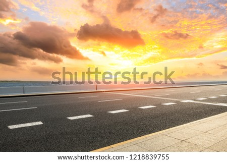 Asphalt road and dramatic sky with coastline at sunset #1218839755