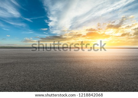 Asphalt road and dramatic sky with coastline at sunset #1218842068