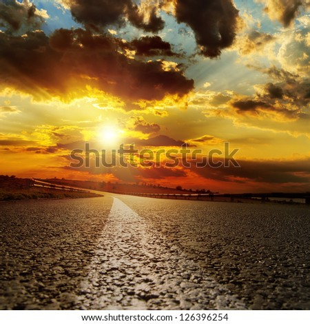 asphalt road and dramatic sunset over it