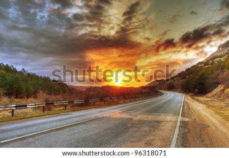 Asphalt road and evening sun in clouds