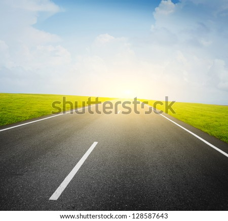 Asphalt road and green meadow and blue cloudy sky