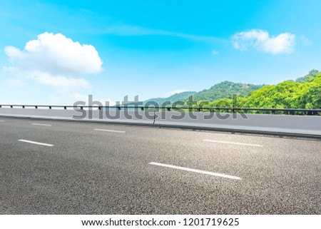 Asphalt road and green mountain under the blue sky #1201719625