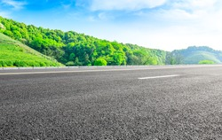 Asphalt road and green tea mountain nature landscape on sunny day.