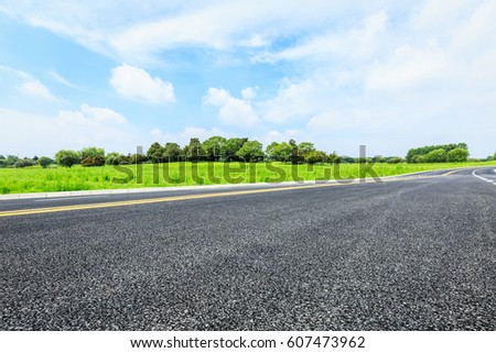 Asphalt road and green trees in the blue sky #607473962
