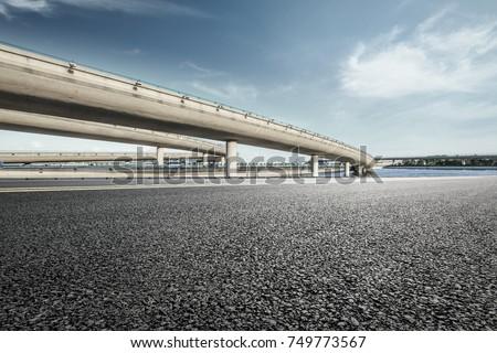 Asphalt road and highway bridge under the blue sky #749773567
