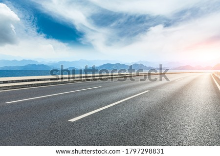 Asphalt road and lake with mountains under blue sky. Foto d'archivio ©