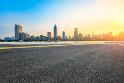 Asphalt road and modern cityscape in Shanghai at sunset