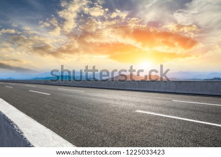 Asphalt road and mountains at beautiful sunset #1225033423