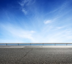 Asphalt road and sea coast line with blue sky on horizon. Landscape in sunny summer day