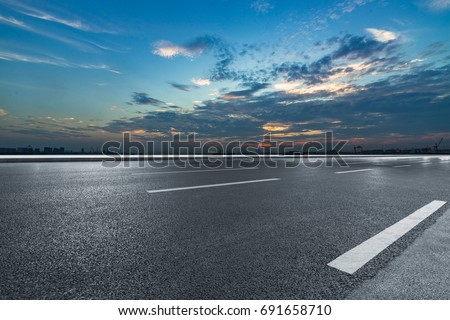 Asphalt road and the beautiful urban skyline at sunset