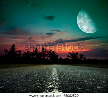 asphalt road and the moon at dusk - stock photo