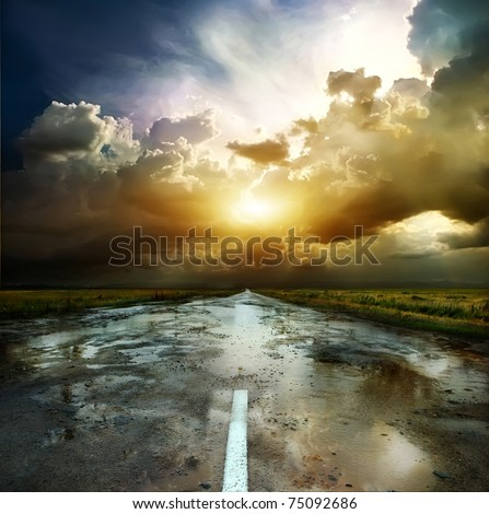Asphalt road and the puddles at sunset