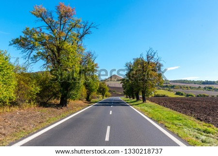 Asphalt road and typical conical volcanic hill of Central Bohemian Highlands on sunny summer day, Czech Republic.