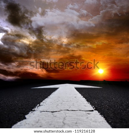asphalt road at dusk with an arrow