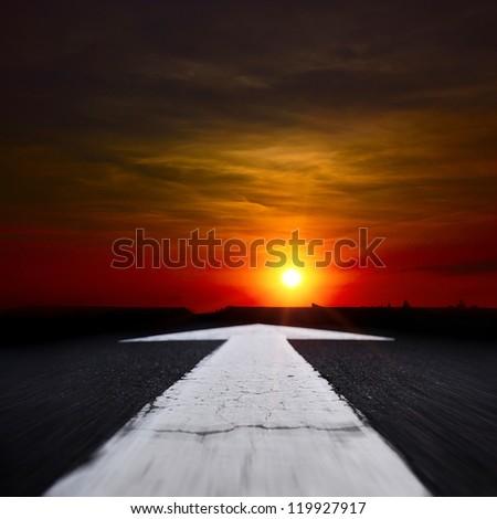 asphalt road at dusk with an arrow