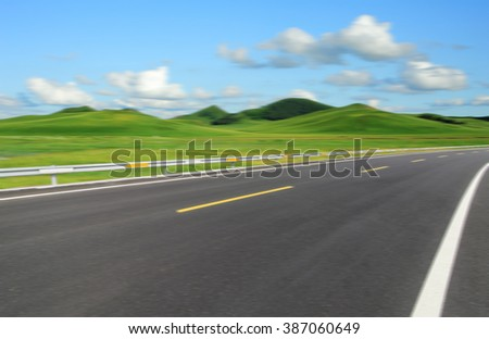 Asphalt road beside green meadow under blue sky. #387060649
