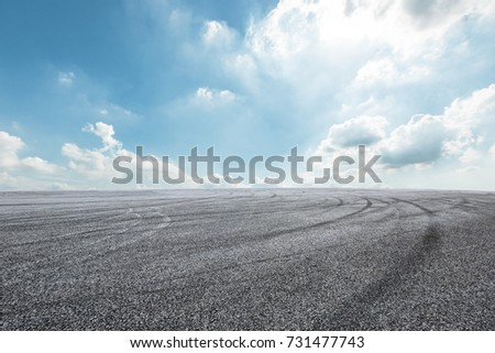 Asphalt road circuit and sky clouds with car tire brake #731477743