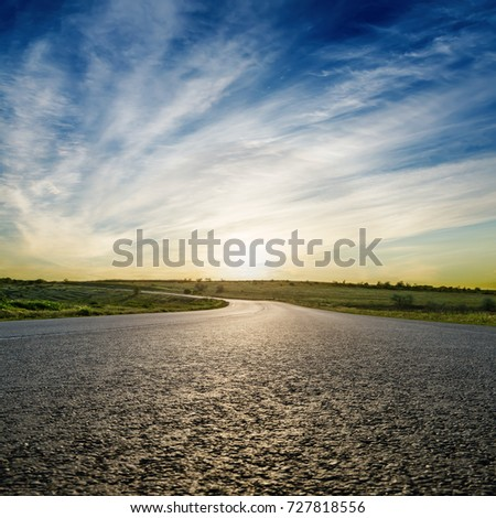 asphalt road closeup and dramatic sunset. soft focus on bottom of picture