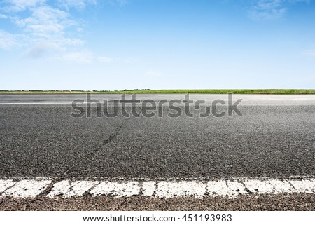 Asphalt road closeup with blue sky on horizon. Selective focus on foreground