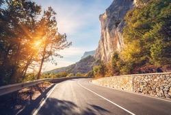 Asphalt road. Colorful landscape with beautiful mountain road with a perfect asphalt. High rocks, trees, blue sky at sunrise in summer. Vintage toning. Travel background. Road at mountains. Sunny road