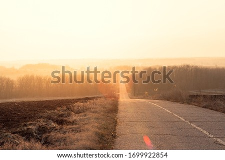 Asphalt road down the hill in Serbia during the winter. Sunrise and frosted grass by the road. Stockfoto ©