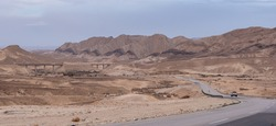 Asphalt road going through the Negev Desert near Big Crater in Israel. Chain of varicolored mountain ridges on the background. Dramatic, colorful and diverse desert landscape. Yellow sandstone hills.
