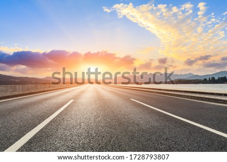 Asphalt road ground and mountain landscape at sunset.