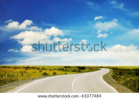 asphalt road in a field