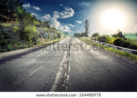 Asphalt road in a mountainous area under a dramatic sky with a huge sun side