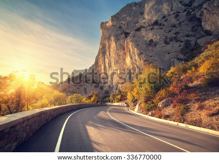 Asphalt road in autumn forest at sunrise. Crimean mountains.