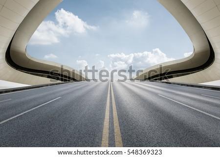 Asphalt road in front of modern bridge construction #548369323