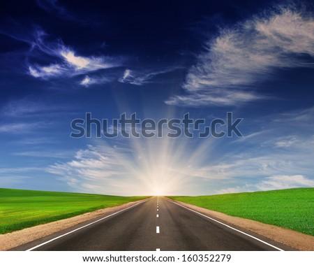 Asphalt road in green fields under beautiful sky. Way