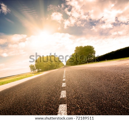 Asphalt road in green meadow. Belarus. Golden sunset.