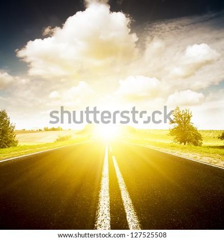 Asphalt road in green meadow. Belarus.  Sunset