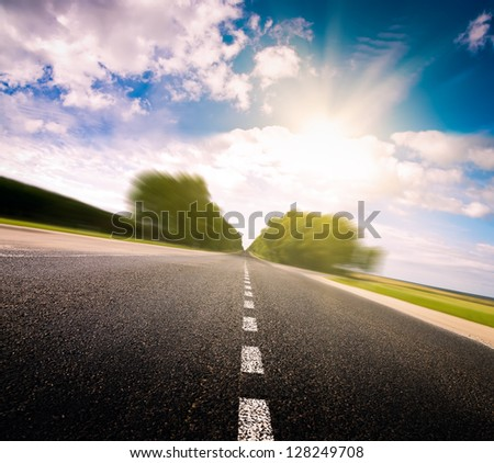 Asphalt road in green meadow. Belarus.  Sunset