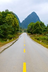 Asphalt Road in mountain area with yellow line in the middle of the road for road background or business concept. Thunder clouds in the sky.