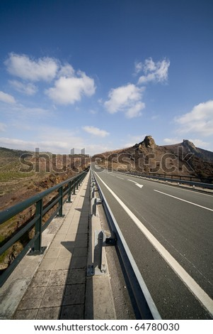 Asphalt road in mountains and blue sky