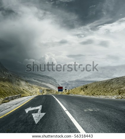 Asphalt road in mountains with arrows and storm dark clouds over valley