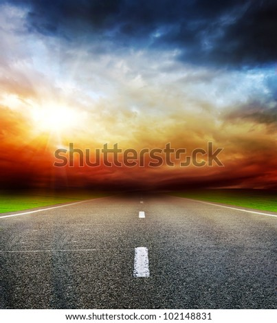 asphalt road in the field over stormy dark cloudy sky during sunset or sunrise