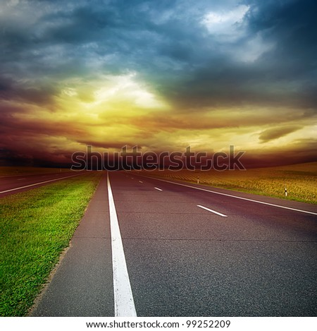 asphalt road in the field over stormy dark cloudy sky - sunset in the evening - stock photo