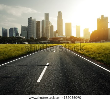 Asphalt road leading to a city with tall buildings through green meadow #132056090